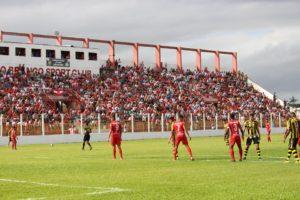 Jogadores do Rio Branco e Cascavel se posicionam no gramado do Estádio Nelson Medrado Dias. Ao fundo, um grande público se faz presente nas arquibancadas do estádio.