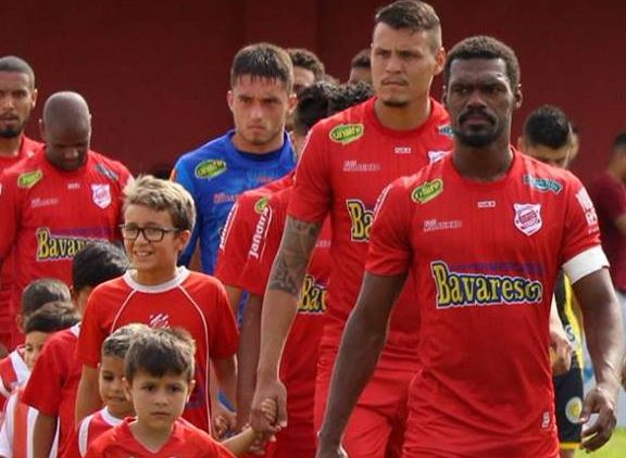 Fila de jogadores do Rio Branco entra no gramado do Estádio Nelson Medrado Dias.