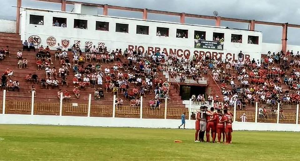 Imagem mostra jogadores do Rio Branco abraçados numa roda no gramado. Ao fundo, arquibancada do Estádio Nelson Medrado Dias conta com bom público.