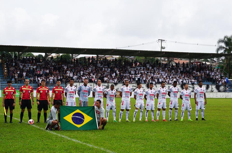 Time do Operário parado em fila durante a execução do hino nacional ao lado dos árbitros escalados para o jogo. Todos estão posicionados atrás de uma bandeira do Brasil. Ao fundo, a arquibancada do Estádio Emílio Gomes está lotada de torcedores do Fantasma.